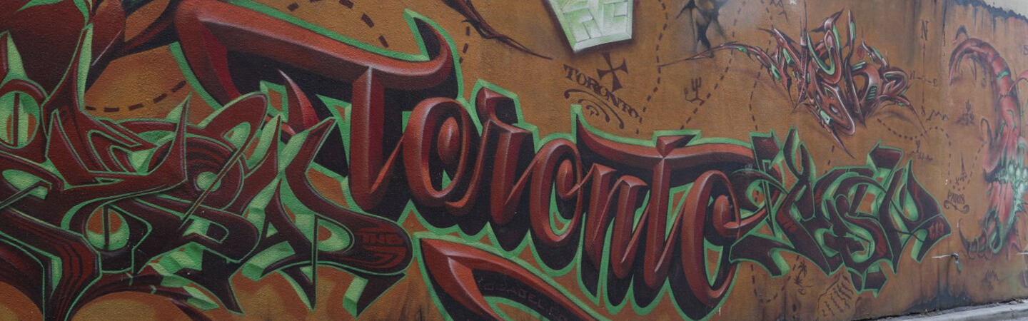 """Large graffiti mural. The background of the mural resembles an old treasure map with an X marking the spot and the word """"Toronto"""" below it. Painted over the map, the mural also features large stylized designs and a large scale stylized painting of the name """"Toronto"""" in green and burgundy."""