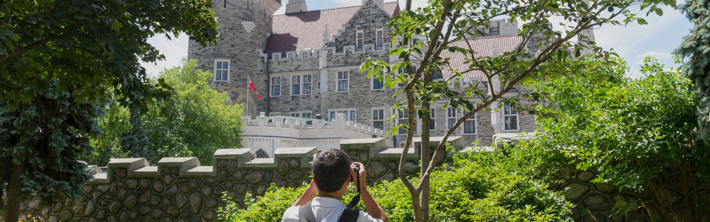 In the foreground, a man in a white t-shirt and black backpack facing away, taking a photo of Casa Loma in the background.
