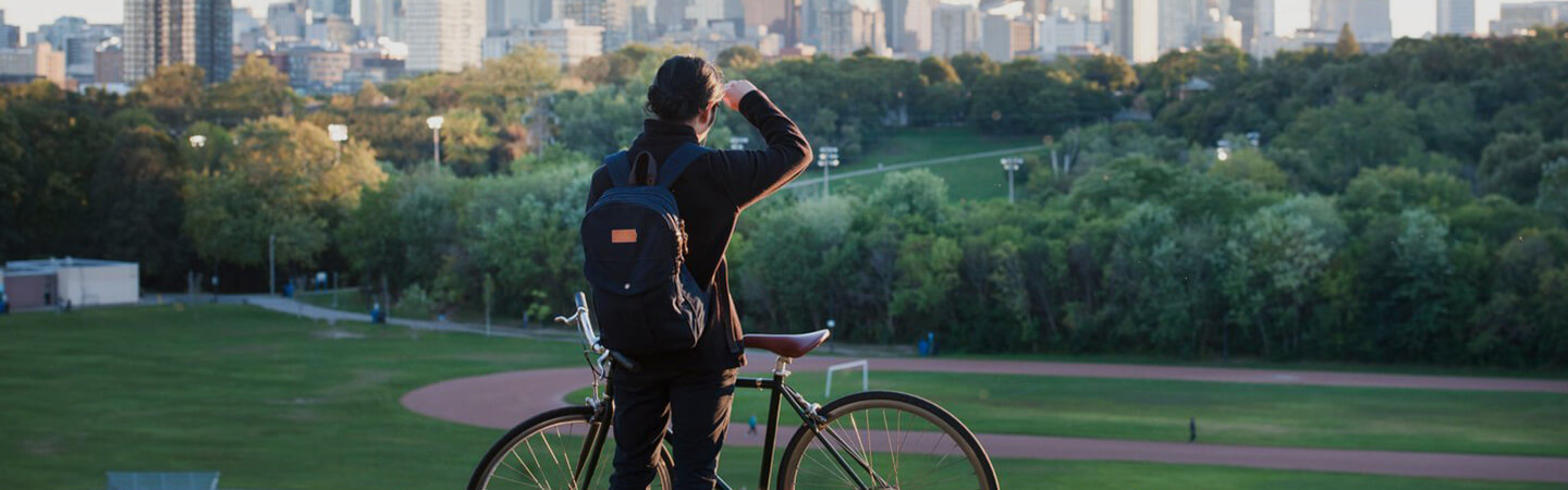 In the foreground, a person stands behind their bicycle facing Riverdale Park and the Don Valley. Lush trees and Toronto's downtown core line the background.