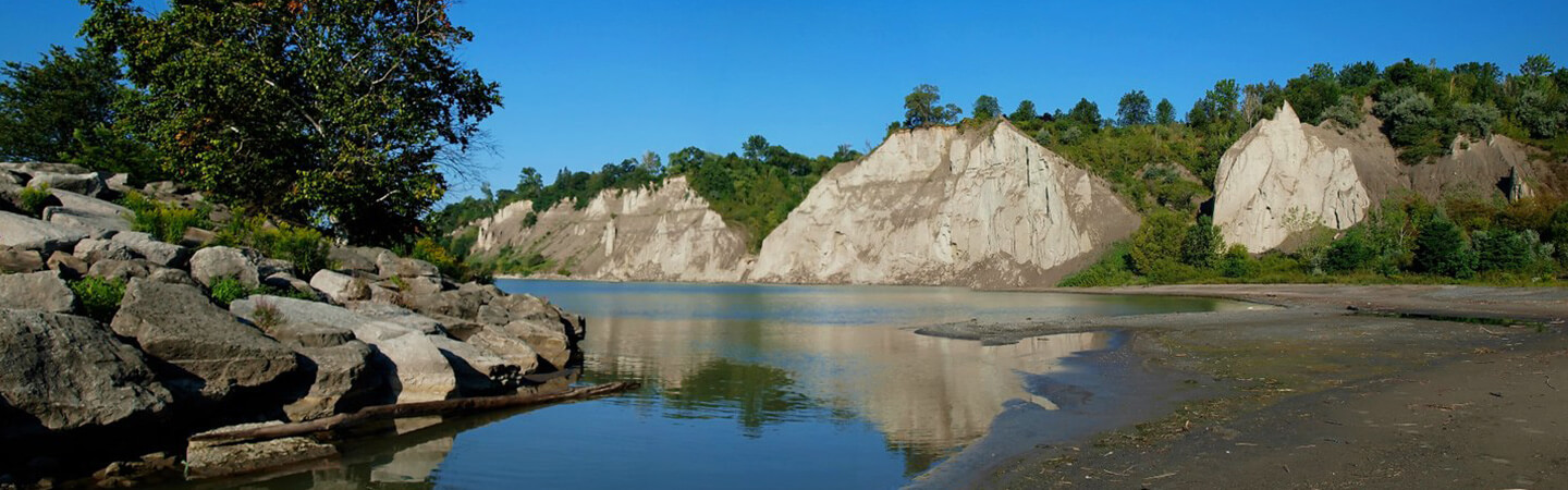 The Scarborough Bluffs line the background overlooking Lake Ontario. In the foreground, boulders line the shoreline on the left and a small beach area to the right.