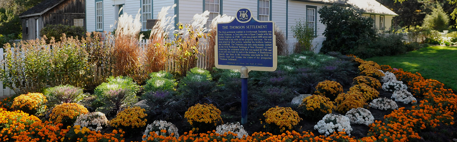 A large lush flower bed sits in front of one of the Scarborough Museum buildings. A white picket fence runs between them. A historic plaque on a post sits in front of the flower bed.
