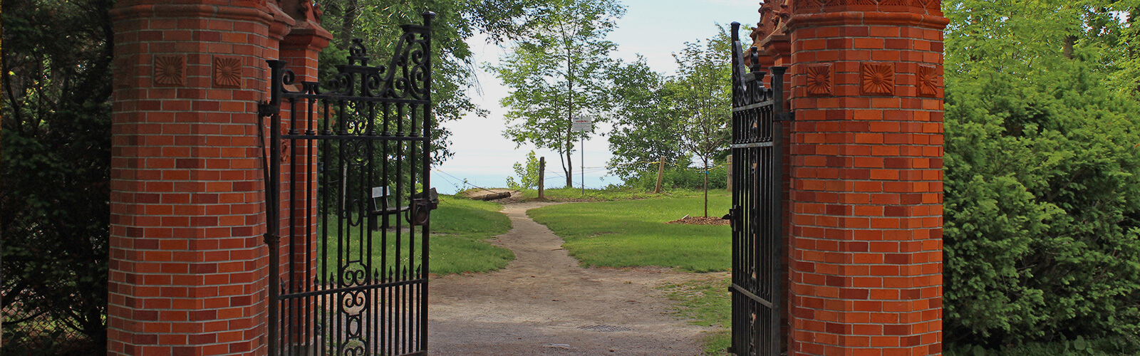 An open old looking and ornate red brick and wrought iron gate leading down a small dirt path toward a cliff edge. Lake Ontario can be seen in the background. Lush trees sit on either side of the gate.