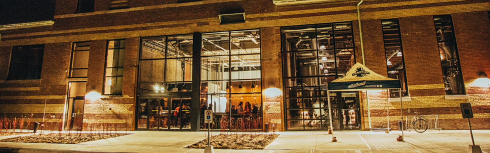 Night-time photo of large industrial looking brick building with several large windows. The interior is well lit, and inside one of the windows, a brewery tank is visible with a promotional tent sitting outside the window. Inside the other windows, a possible seating area with glimpses of people sitting and standing around.