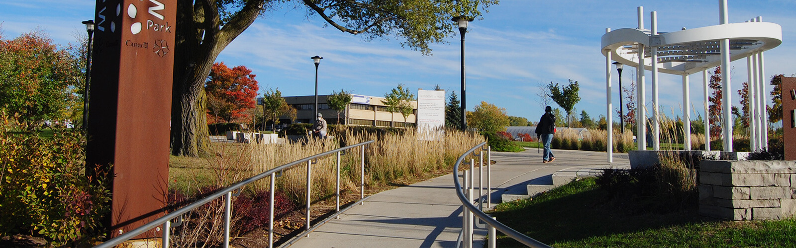 Paved ramp with metal railings on either side runs through the middle of the photo from the foreground. It leads to a paved area with a contemporary gazebo structure. Shrubs, trees and other greenery line the ramp on either side. Person can be seen walking toward the ramp in the centre.